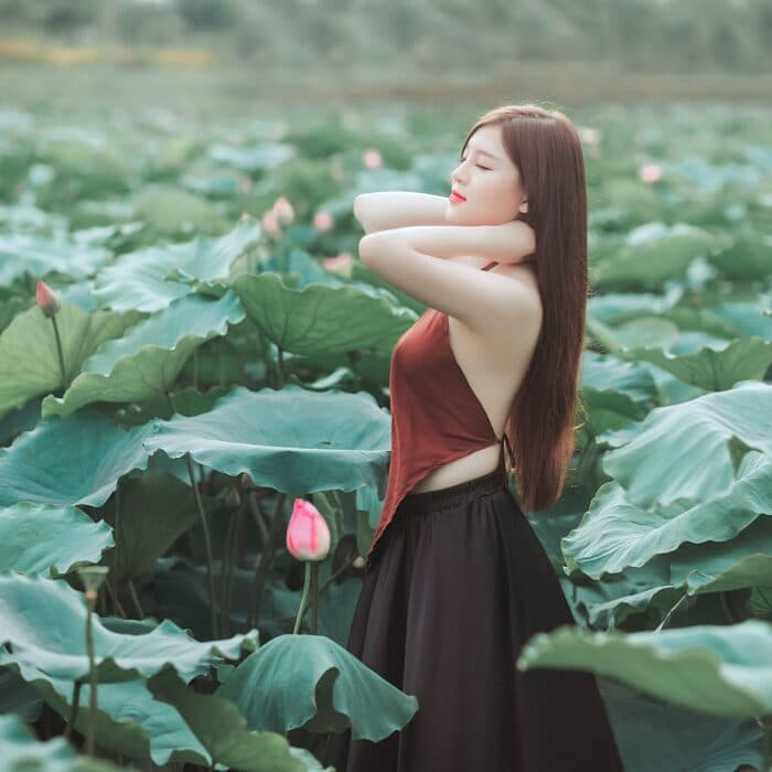 woman surrounded by large leaves in sun, relaxed