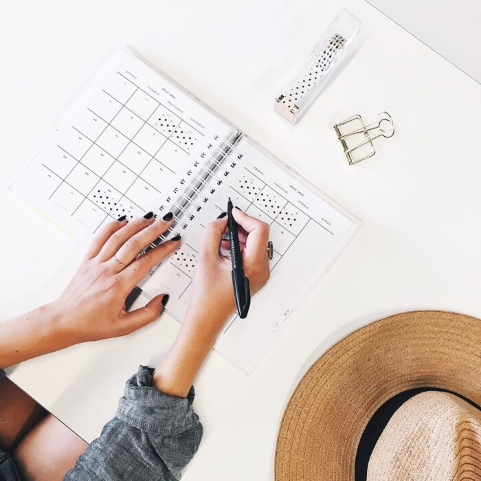 woman writing in her schedule day planner