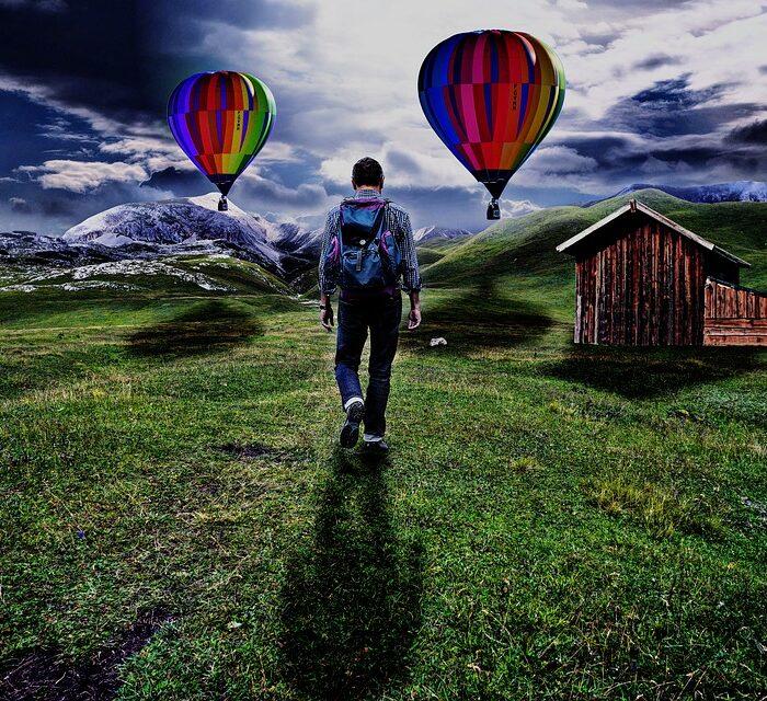 man walking toward cabin and hot air balloons