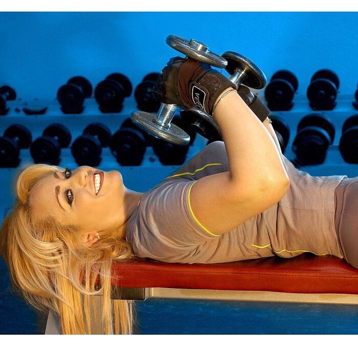 woman lifting weights at gym, smiling at camera, fitness
