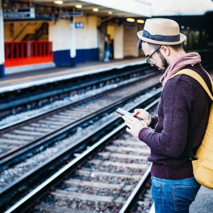man on phone while standing at train station