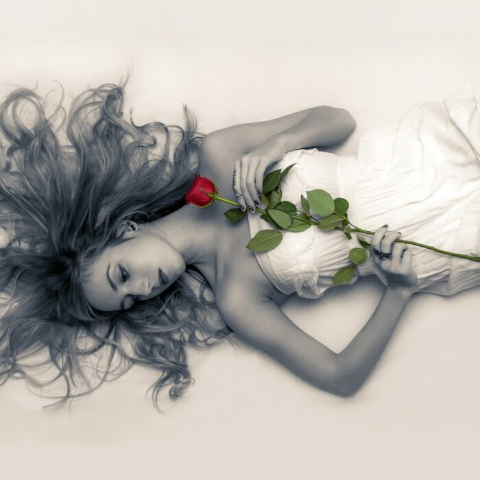 woman laying on the ground with a red rose