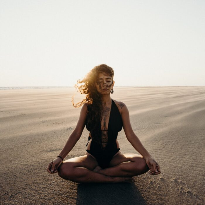 woman meditating in the sand, inflluencer