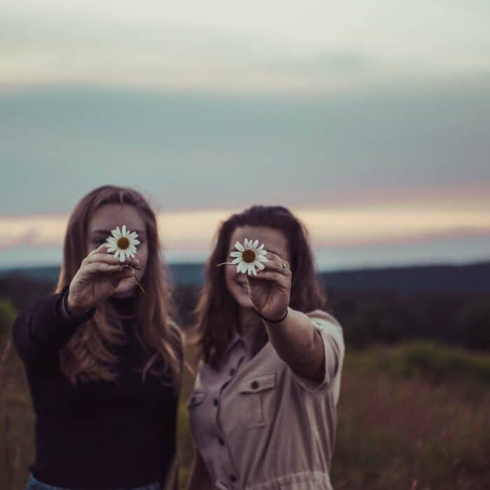 two women holding flowers friends influencer