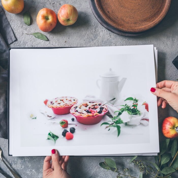 woman holding pictures of pie with apples portfolio