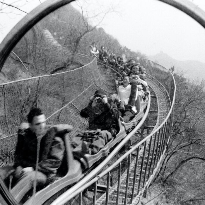 people on a roller coaster with a mirror
