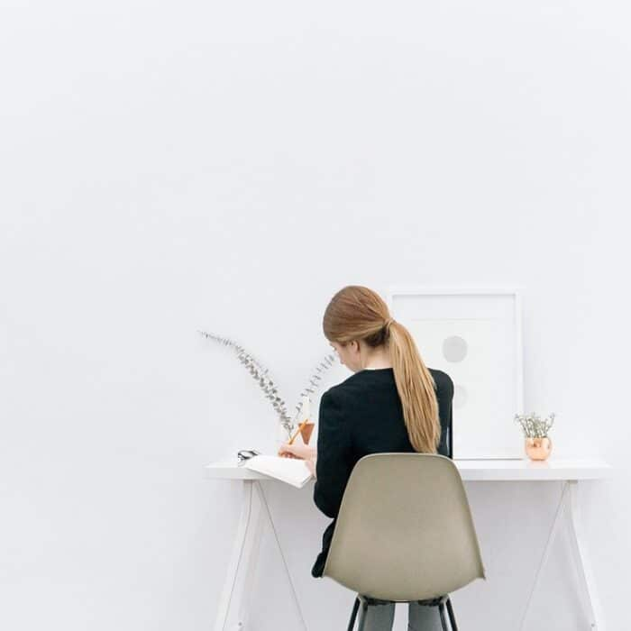 woman writing in a journal in a white room planning