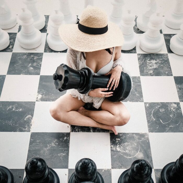 woman holding a chess piece on a chessboard