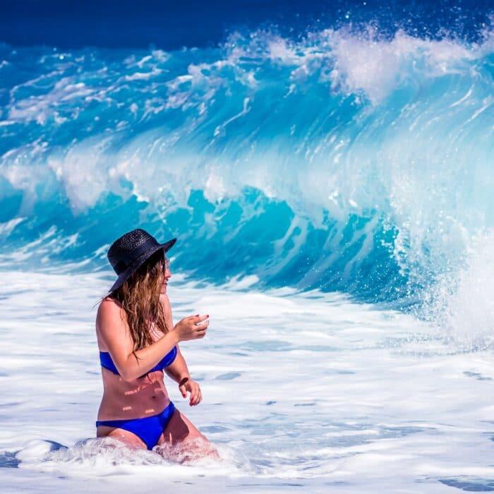 woman in the waves walking bikini bright
