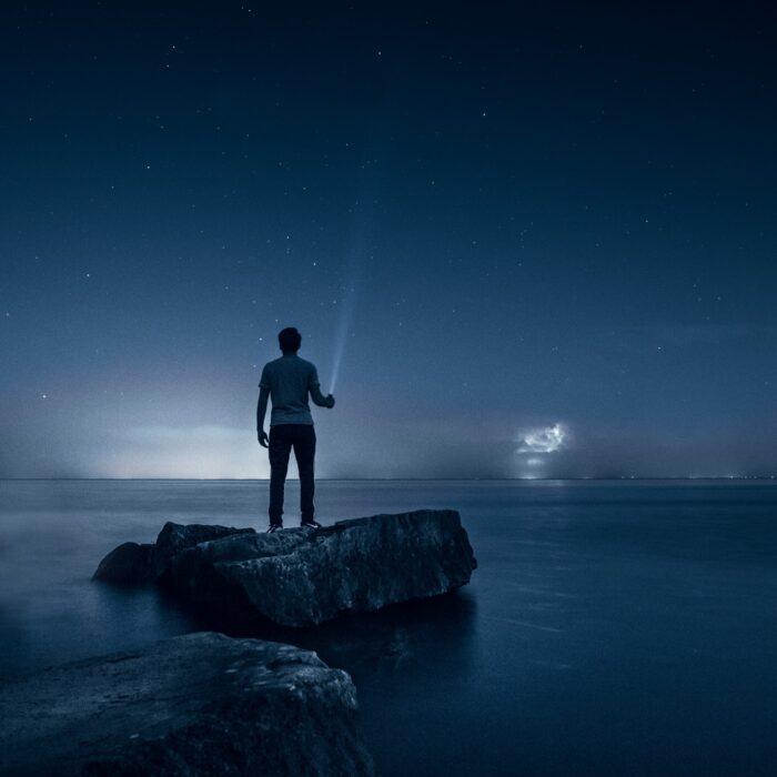 man holding a flashlight at a beach