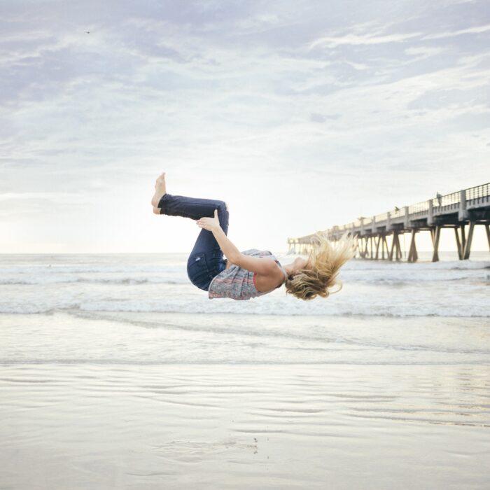woman doing a backflip off a dock at beach