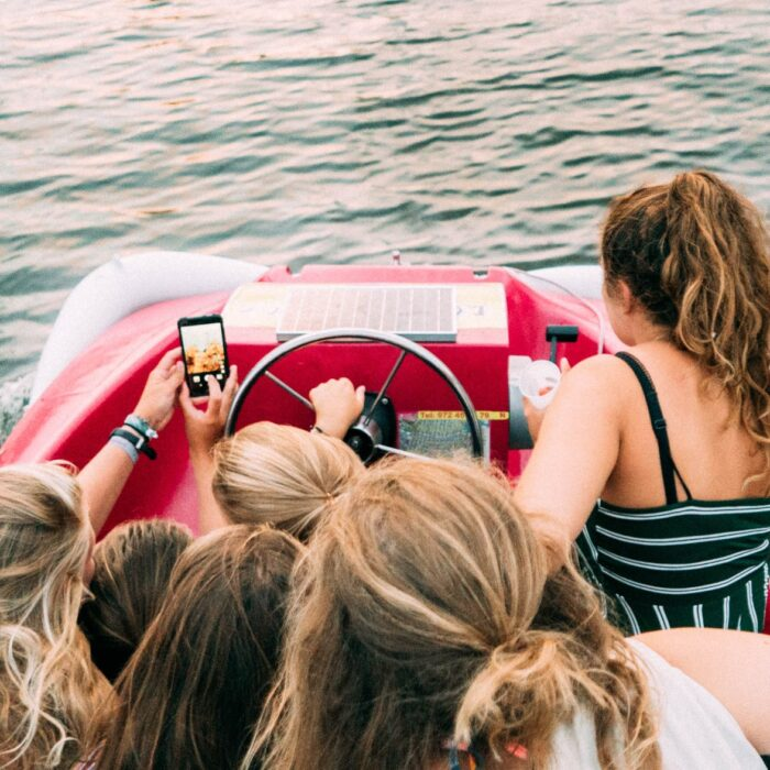 women on boat with mobile phone selfie