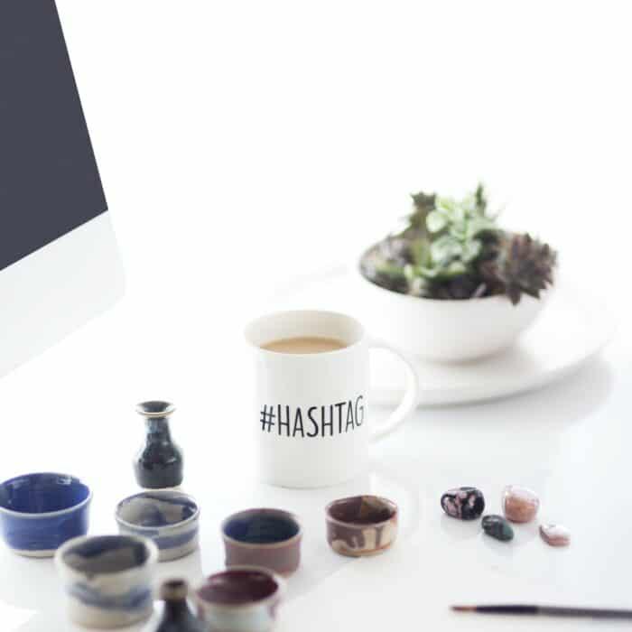 hashtag coffee mug with paints around it
