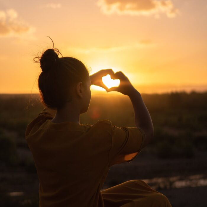 woman creating a heart with her hands in the sun influencer