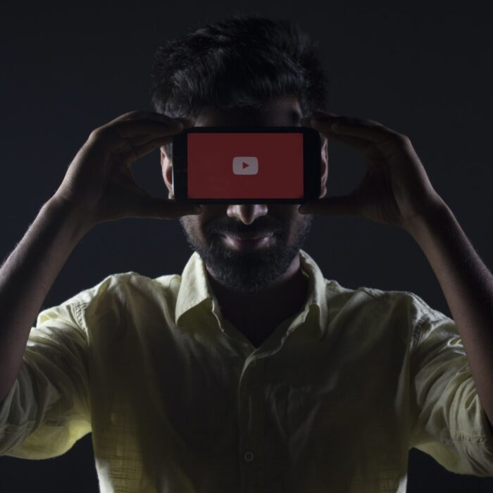 man holding youtube mobile phone up to face
