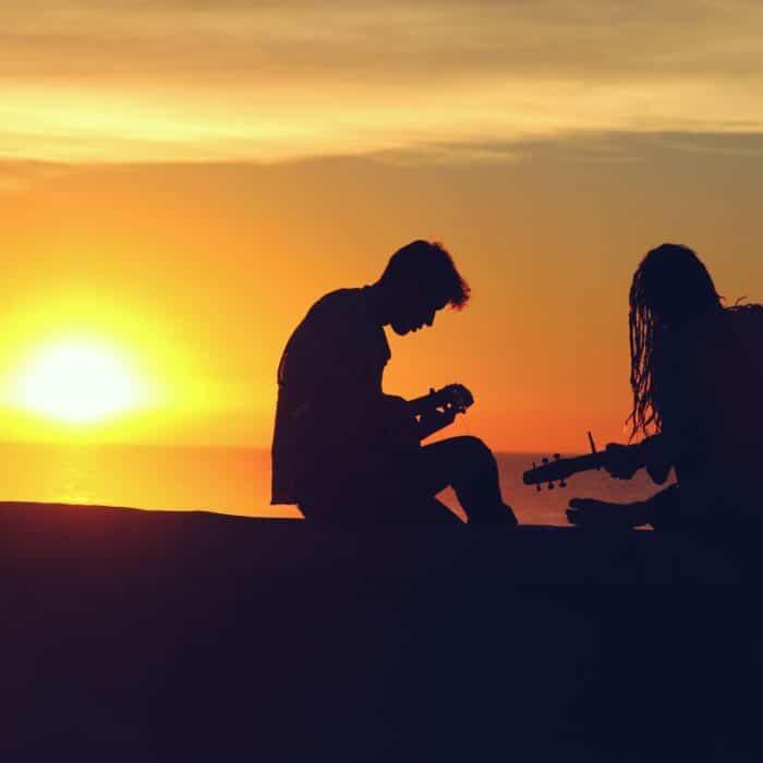 music on beach sunset couple man woman