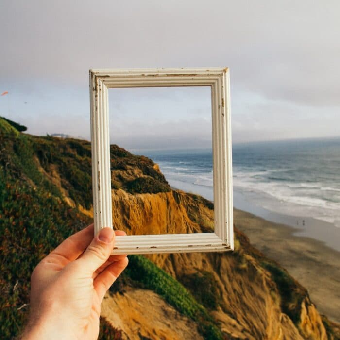someone holding a picture frame looking at a landscape