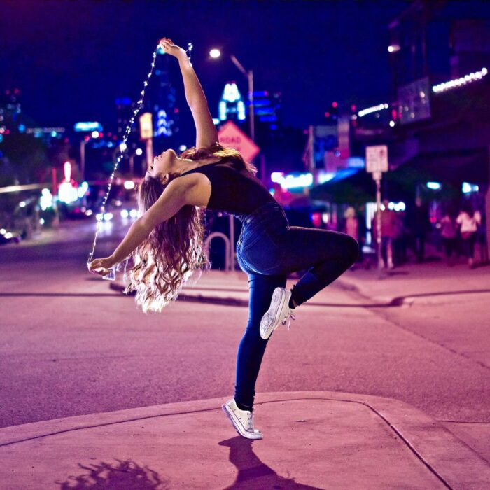 woman dancing in the street with a string of lights