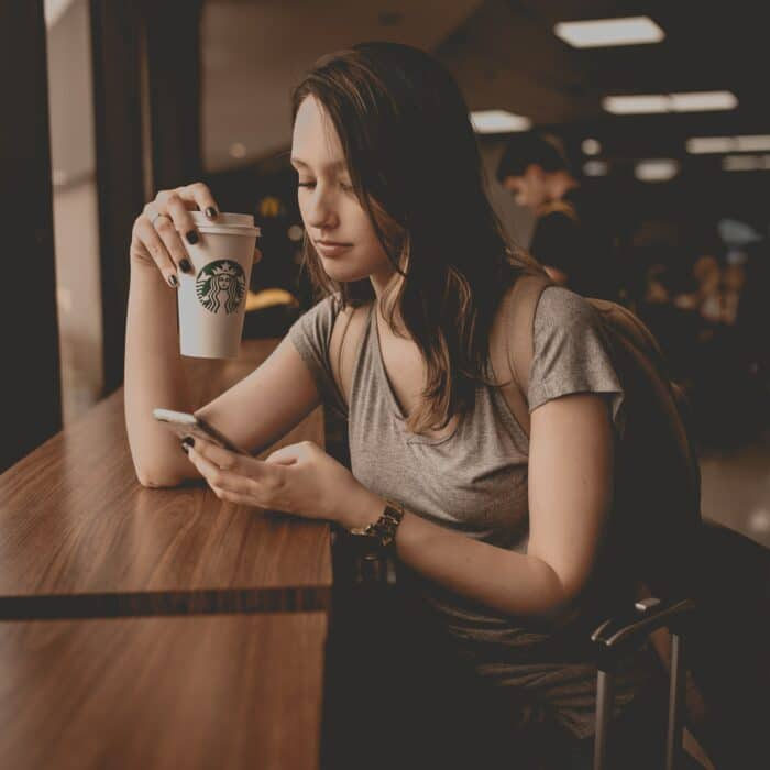 woman with coffee cup and mobile phone