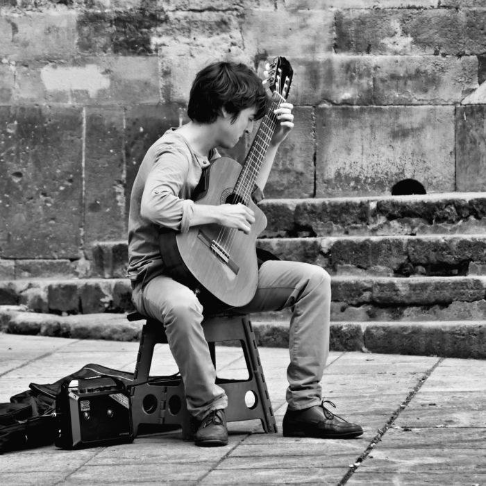black and white man playing guitar