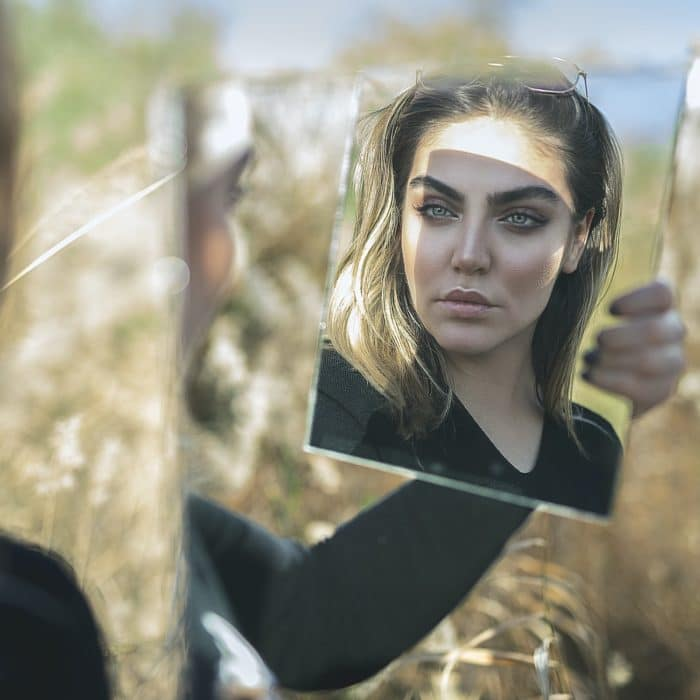 woman holding a mirror in a field