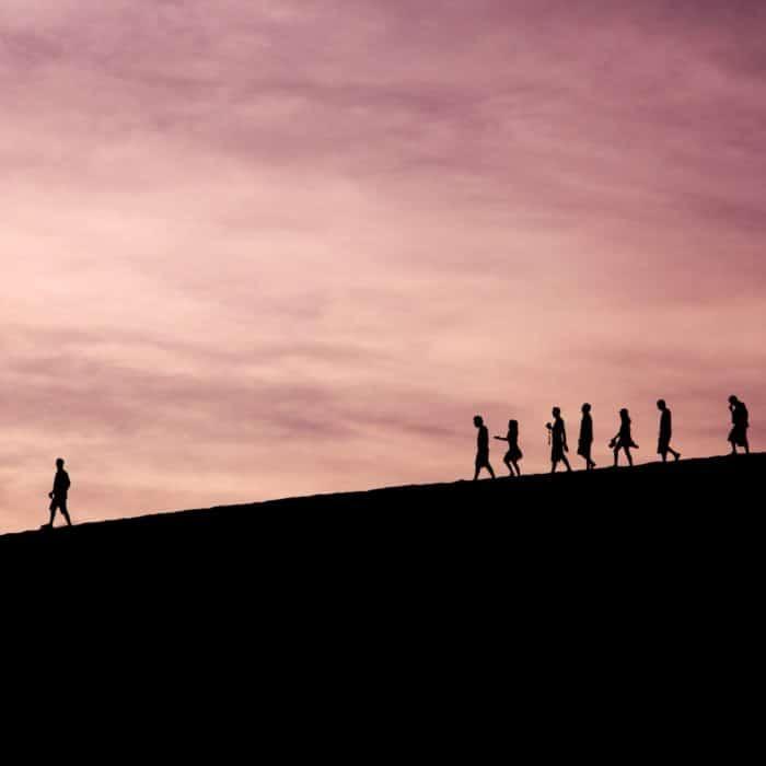 pink sky 7 silhouette people following a single man