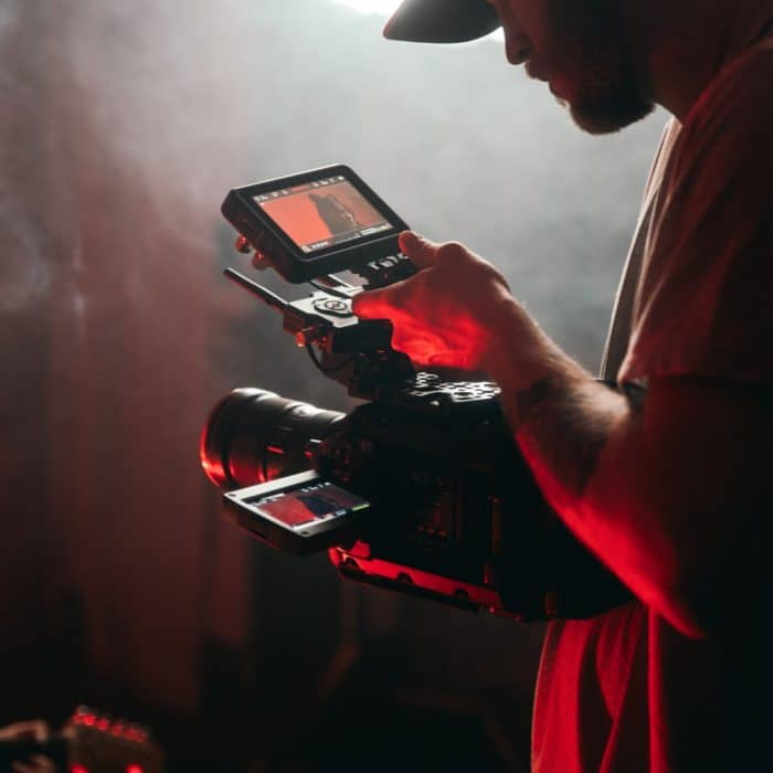 man holding video camera. red glow