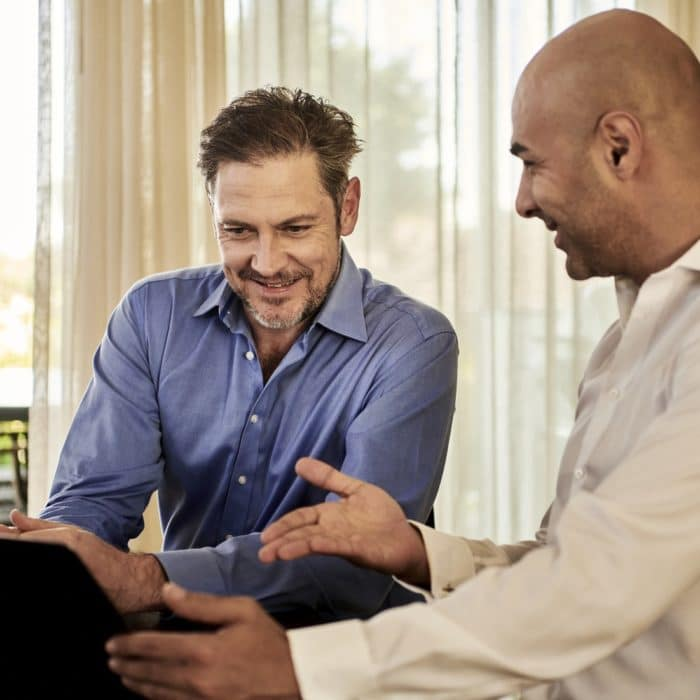 man showing another man how to use computer