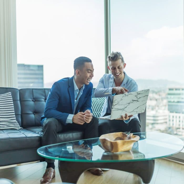 two men having a meeting in front of sky view window