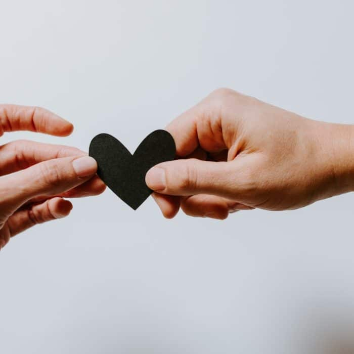 two people holding a black heart