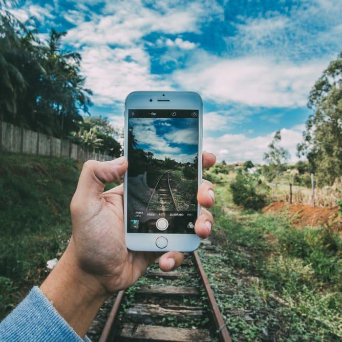 person taking photo of railroad track