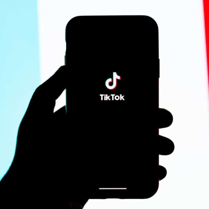 tik tok on phone with blue, white, and red background