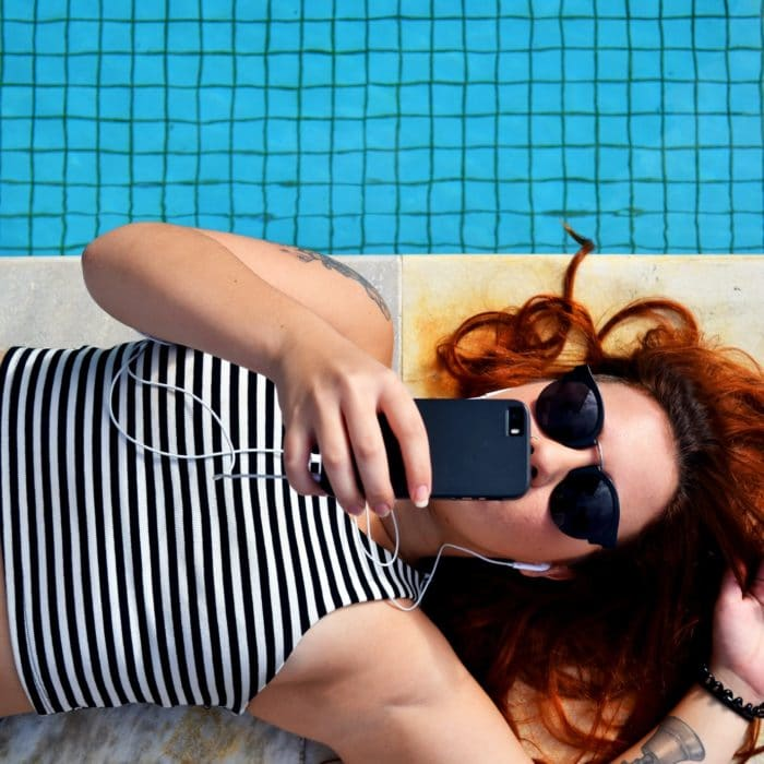 woman laying by pool with phone